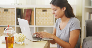 Hispanic woman using laptop on coffee table